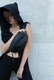 ragazza con una piccola borsa vicino alla parete Immagini Stock