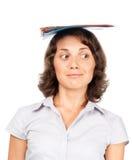 Ragazza con una pila di dispositivi di piegatura di carta sulla sua testa Fotografie Stock Libere da Diritti