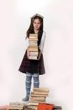Ragazza con una pila di libri Fotografia Stock