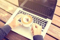Ragazza con una tazza di caffè e un computer portatile alla mattina Fotografie Stock Libere da Diritti