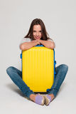 Ragazza con una valigia gialla Immagini Stock
