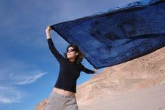 Ragazza con uno scialle blu un giorno ventoso. Fotografia Stock