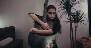 Ragazza con uno sguardo triste con la chitarra Ragazza con un considerare il fronte dipinto video d archivio