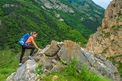 Ragazza con uno zaino nelle montagne fotografia stock libera da diritti