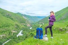 Ragazza con uno zaino nelle montagne fotografia stock