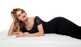 Ragazza con vetro di champagne che si trova sulla pelliccia, portante un vestito nero Fotografia Stock