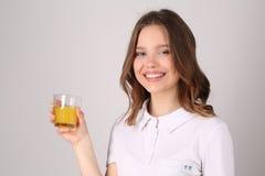 Ragazza con vetro di succo Fine in su Priorità bassa bianca Immagine Stock