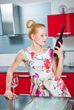 Ragazza con vetro e la bottiglia di vino in cucina Fotografie Stock