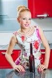 Ragazza con vetro e la bottiglia di vino in cucina Fotografia Stock