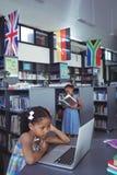 Ragazza concentrata che esamina computer portatile in biblioteca Fotografia Stock