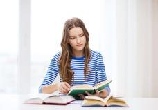 Ragazza concentrata dello studente con i libri Immagine Stock