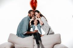 Ragazza contenta che dimostra il segno di amore mentre famiglia che riposa sul sofà fotografia stock
