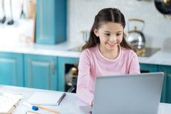 Ragazza contenta che lavora al suo computer portatile Fotografie Stock
