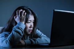 Ragazza coreana asiatica preoccupata dello studente che sembra studio diminuito e disperato con il computer portatile nello sforz Immagini Stock Libere da Diritti