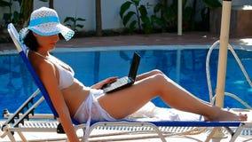 Ragazza in costume da bagno che si trova sulla chaise-lounge del sole lo stagno archivi video