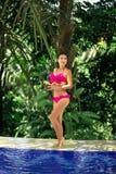 Ragazza in costume da bagno rosa che posa allo stagno fotografia stock libera da diritti