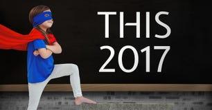 Ragazza in costume del supereroe che sta vicino ad un bordo con le citazioni di 2017 nuovi anni Immagine Stock