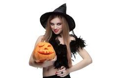 Ragazza in costume della strega con la zucca di Halloween Immagine Stock