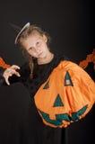 Ragazza in costume di Halloween con la zucca su fondo nero Immagine Stock
