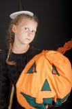 Ragazza in costume di Halloween con la zucca su fondo nero Immagini Stock