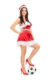 Ragazza in costume di Santa con calcio al di sotto del suo piede Immagine Stock