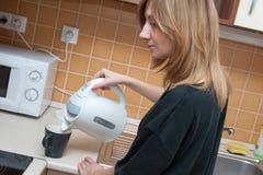 Ragazza in cucina che produce tè Immagine Stock