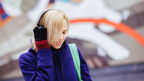 Ragazza in cuffie che ascolta la musica su fondo confuso Immagini Stock