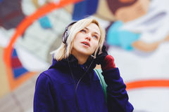 Ragazza in cuffie che ascolta la musica su fondo confuso Fotografia Stock Libera da Diritti
