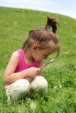 Ragazza curiosa con i fiori d'esame della lente d'ingrandimento nell'erba a tempo di primavera Immagine Stock Libera da Diritti