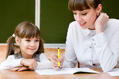 Ragazza d'aiuto dell'insegnante con la lezione di scrittura Immagine Stock Libera da Diritti