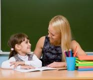 Ragazza d'aiuto dell'insegnante con la lezione di scrittura Immagini Stock Libere da Diritti