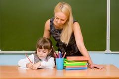 Ragazza d'aiuto dell'insegnante con la lezione di scrittura Fotografia Stock Libera da Diritti