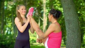 Ragazza d'aiuto dell'istruttore personale in gamba che allunga allenamento Allenamento di forma fisica all'aperto video d archivio