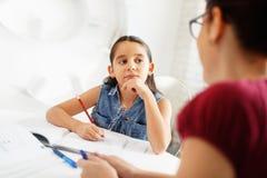 Ragazza d'aiuto della madre ispana che fa compito della scuola a casa immagine stock libera da diritti