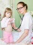 Ragazza d'esame di medico con lo stetoscopio immagini stock libere da diritti