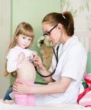Ragazza d'esame di medico con lo stetoscopio fotografia stock libera da diritti