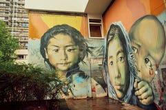 Ragazza da una famiglia di rifugiato sulla parete con arte della via fotografia stock libera da diritti