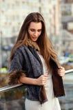 Ragazza dai capelli lunghi alla moda vestita in vestito e breve cappotto di pelle di pecora con le pose della pelliccia nella via fotografia stock libera da diritti