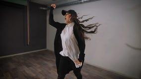 Ragazza dai capelli lunghi in camicia bianca, pantaloni neri, rivestimento e berretto nero saltanti e mostranti dancing moderno d video d archivio