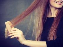 Ragazza dai capelli lunghi che pettina i suoi capelli di bellezza Fotografia Stock