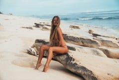 Ragazza dai capelli lunghi terribile sexy che si siede sulla spiaggia su una roccia e su una posa rocciose Il vento gioca con cap immagini stock libere da diritti