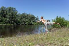 Ragazza dai capelli rossi che fa yoga sulla sponda del fiume su un fondo degli alberi un giorno soleggiato di estate fotografie stock libere da diritti