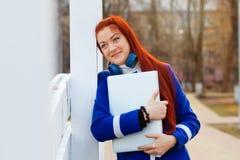 Ragazza dai capelli rossi con le cuffie in un cappotto blu nei sogni e negli abbracci del parco di autunno un computer portatile immagine stock