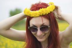Ragazza dai capelli rossi con una corona dei denti di leone su lei capa Immagini Stock Libere da Diritti