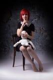 Ragazza dai capelli rossi mistica e bambola su una sedia Fotografia Stock Libera da Diritti