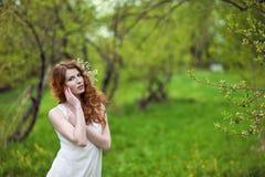 Ragazza dai capelli rossi in un giardino della molla Fotografie Stock Libere da Diritti