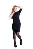 Ragazza dai capelli rossi in vestito nero isolato su fondo bianco Fotografie Stock