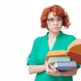 Ragazza dai capelli rossi in vetri con i libri Immagine Stock