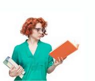 Ragazza dai capelli rossi in vetri con i libri Immagini Stock