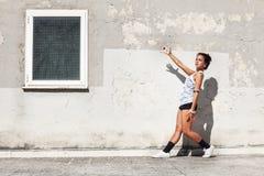 Ragazza davanti a e vecchia parete che indicano una finestra con un braccio Fotografia Stock Libera da Diritti